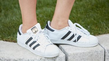 Woman with white Adidas superstar sneakers